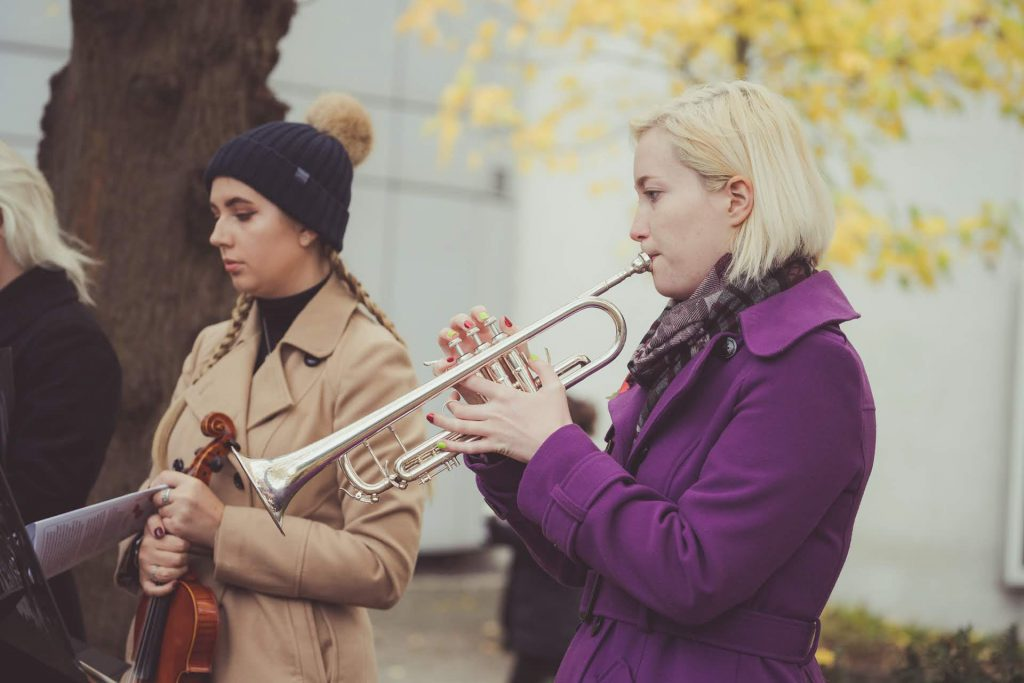 2 females 1 playing trumpet 1 holding violin