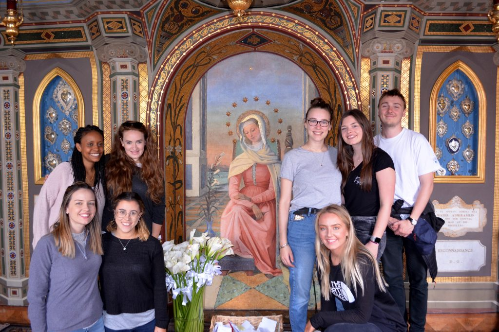 Group of 8 young adults in front of Medieval painting of woman.