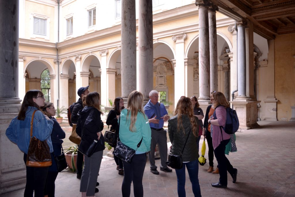 Group of ten with tour guide beside historic building with columns