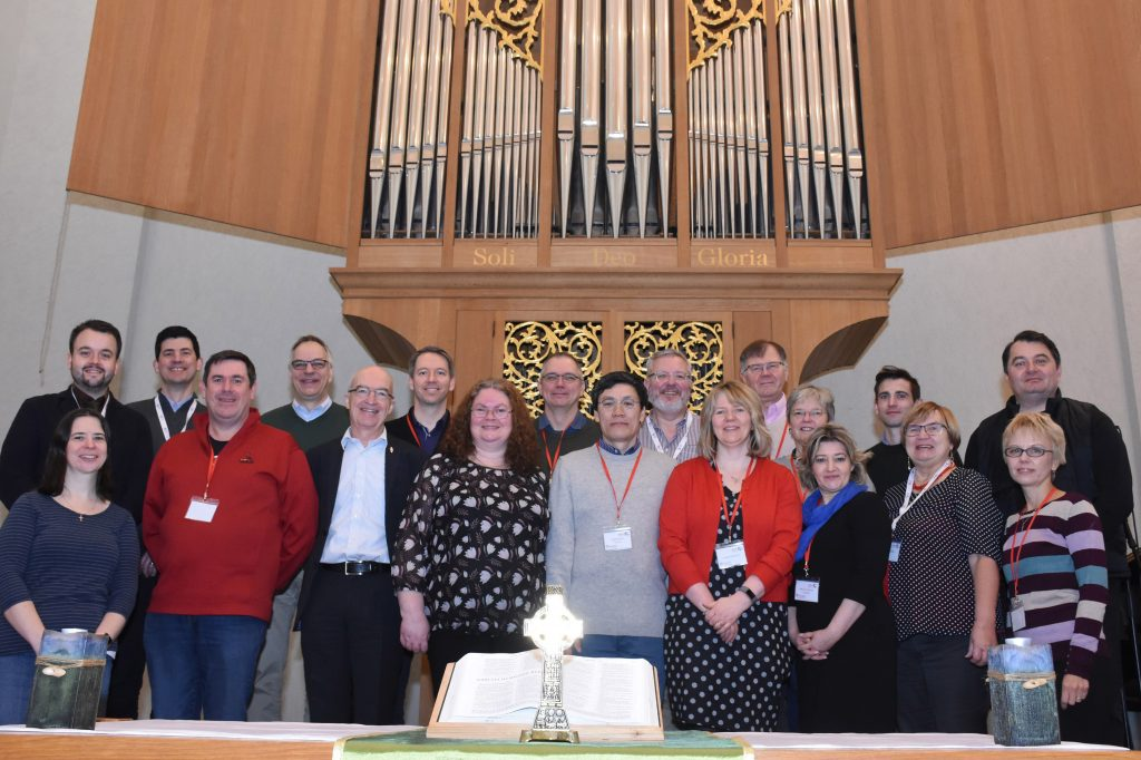Group of 19 white people standing in front of a church organ.