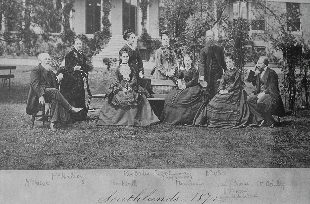 Black and white photo of nine people in the 1870s.