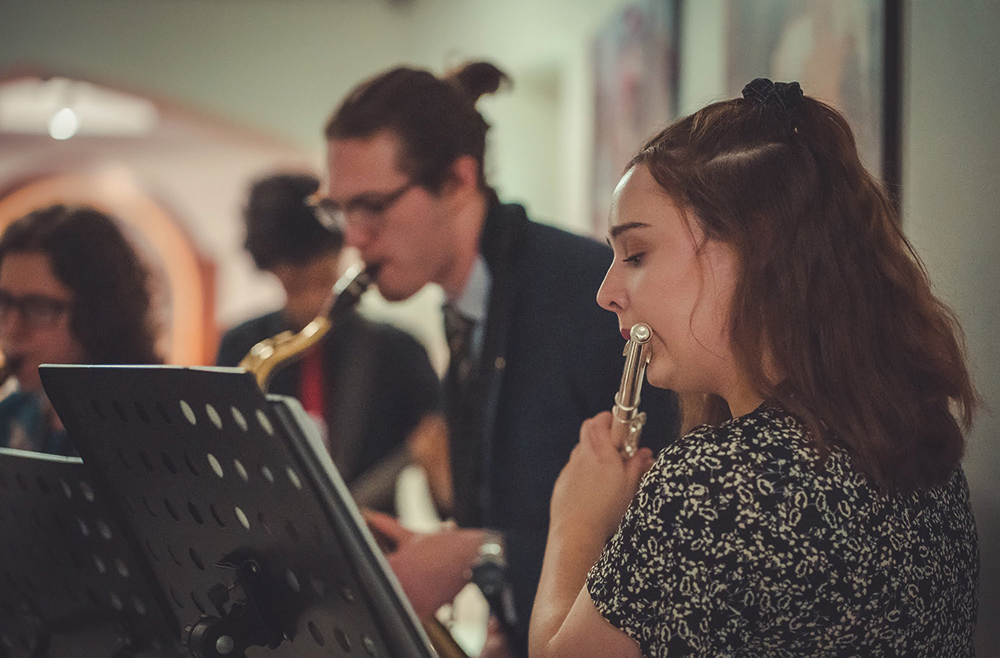 A woman playing the flute and a man playing the saxophone with other musicians in background
