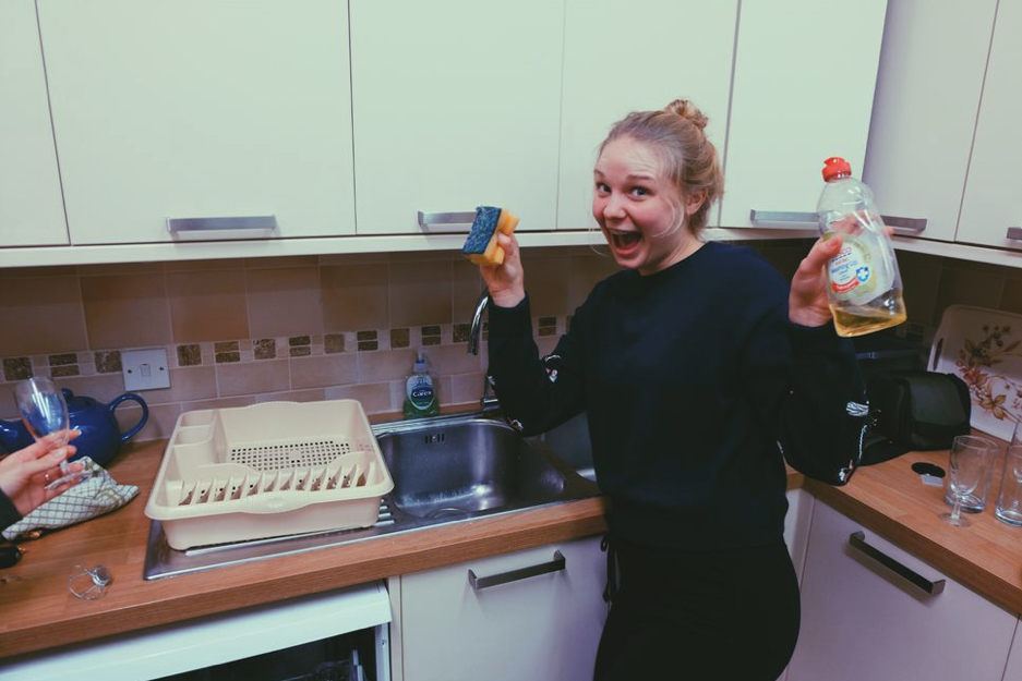 Smiling young woman holding up sponge and washing liquid in kitchen