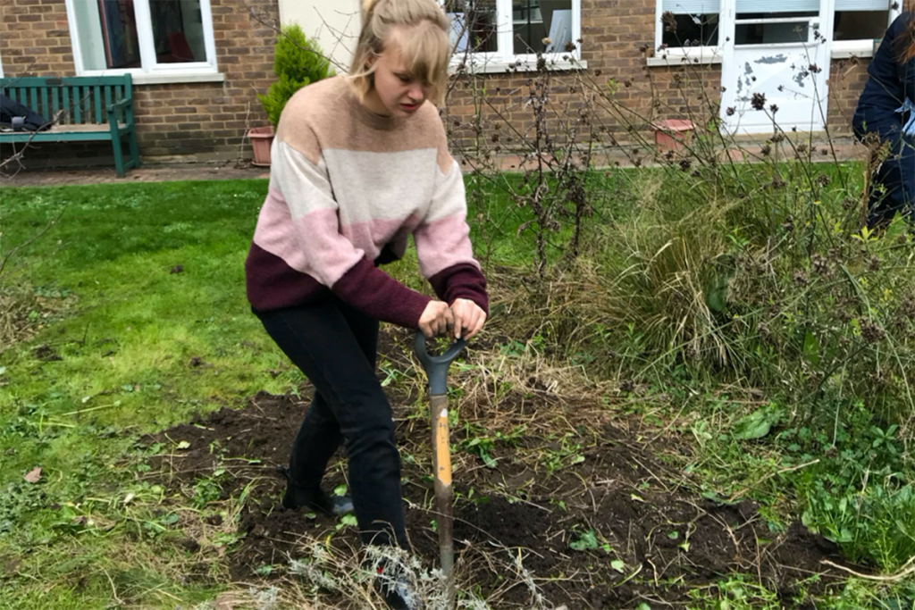 Woman digging in garden with spade