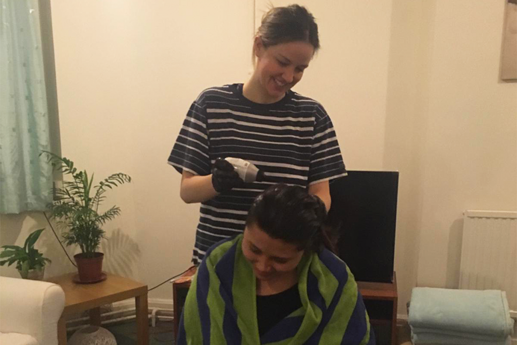 Woman dying another's hair in a living room