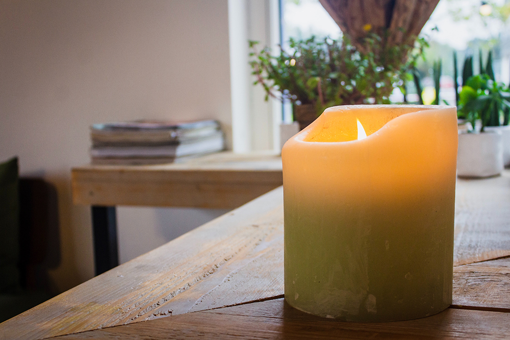 Lit yellow candle on wooden table