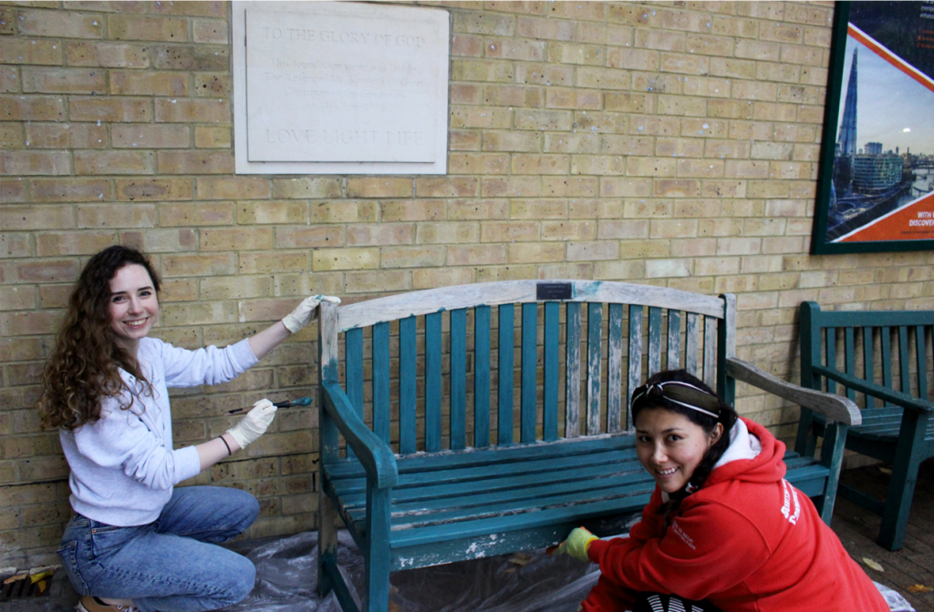 Two female students painting a wooden bench