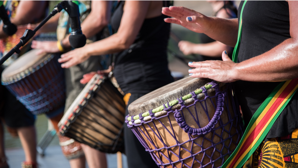 Several people playing african drums